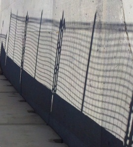 The fencing along the Grand Prix route casts an ominous shadow over the sidewalk.
